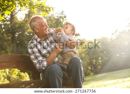 Playful grandfather spending time with his grandson in park - stock photo