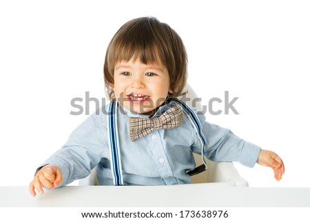 Playful happy baby boy, Child Model with romantic Fashion outfit suspenders and tie bow, delighted and smiling. Studio shot, isolated, over white background with copy space - stock photo