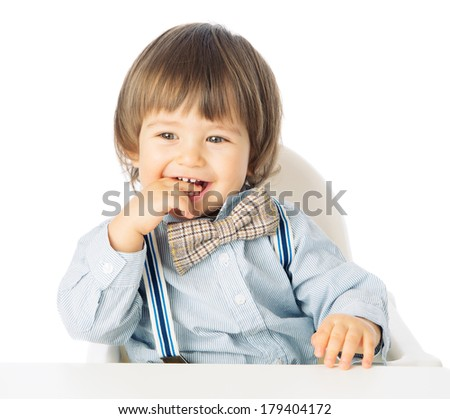 Playful happy baby boy holding hands in the mouth, Child Model with romantic Fashion outfit suspenders and tie bow, delighted and smiling. Studio shot, isolated, over white background with copy space - stock photo