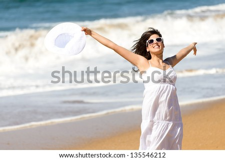 Playful happy woman jumping, running and dancing on beach. Happiness on summer vacation. Caucasian beautiful girl smiling and raising arms, holding white hat.