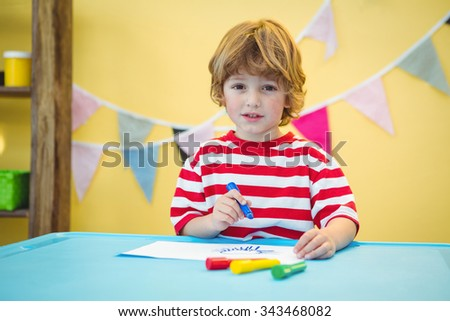 Playful kid colouring in a picture at the desk - stock photo
