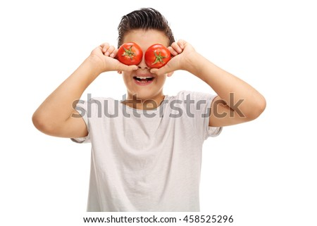 Playful kid holding two tomatoes on his eyes and smiling isolated on white background - stock photo