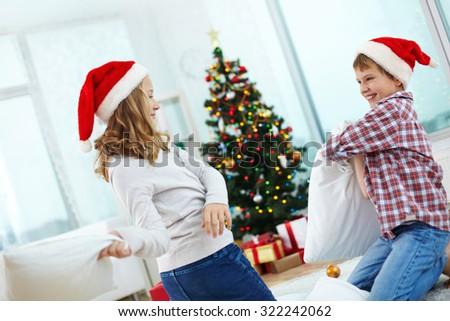 Playful kids in Santa caps having pillow fight - stock photo