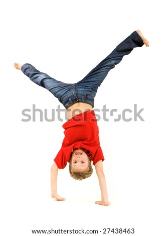 Playful lad standing on his arms with legs pointing upwards over white background - stock photo
