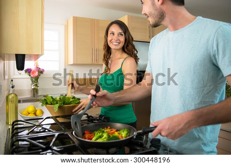 Playful lifestyle cooking at home man and woman flirting and in love  - stock photo
