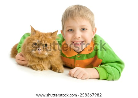 Playful little boy and serious red cat lying down the floor - stock photo