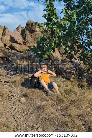 Playful little boy sitting waiting on a mountain slope leaning back on his rucksack as he takes a break during a hiking trip on a hot summer day - stock photo