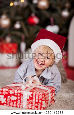 Playful little boy with a mischievous happy grin in a Santa Hat lying on the floor in front of the Christmas tree with a large gift-wrapped present - stock photo