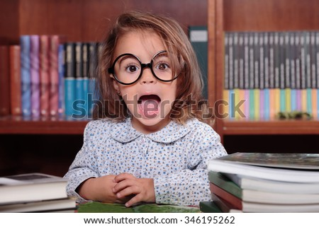 Playful little girl in glasses sitting at teacher's table against of shelves with books