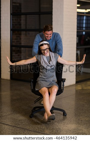 Playful man pushing female colleague sitting on chair in creative office