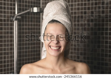 Playful mischievous naked woman with her wet hair in a towel giving the camera a big cheesy grin with her eyes closed as she stands in the bathroom, candid portrait - stock photo