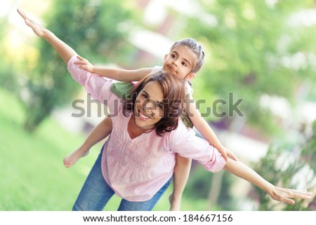 Playful mother and little daughter enjoying in nature. - stock photo