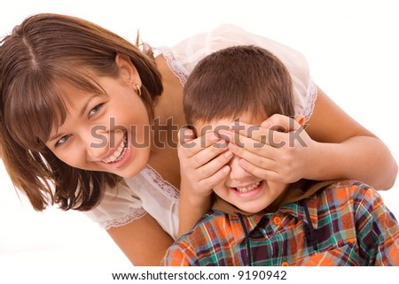 Playful mother and son isolated playing hide-and-seek - stock photo