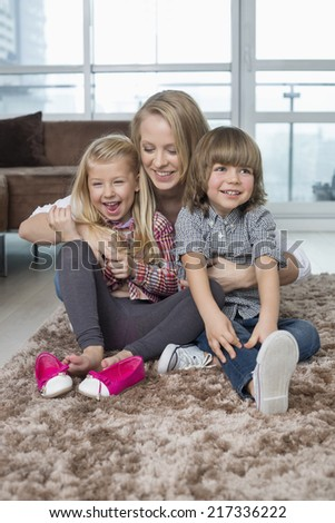 Playful mother with children sitting on rug in living room - stock photo