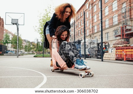 Playful photo of two women outdoors. Young woman sitting on longboard being pushed by her friend along the road. - stock photo