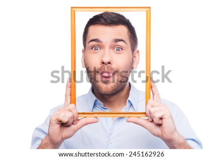 Playful portrait Handsome young man in shirt sticking his tongue out and holding picture frame in front of his face while standing against white background  - stock photo