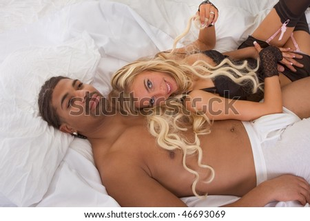 Playful sensual heterosexual couple - Caucasian woman and ethnic black man of mixed African-American and Italian ethnicity - stock photo