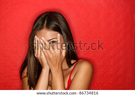 Playful shy woman hiding face laughing timid. Cute Chinese Asian / Caucasian woman smiling happy through hands. Red background. - stock photo