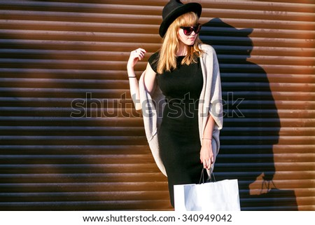 Playful shy woman hiding shopping pack,laughing timid.Cute Chinese Asian / Caucasian woman smiling happy through hands.wall background.black hat,grey coat,black dress,autumn clothes.warm winter style  - stock photo