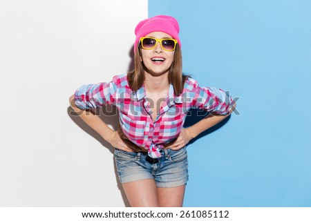 Playful smile. Playful young woman in headwear and glasses posing against colorful background - stock photo