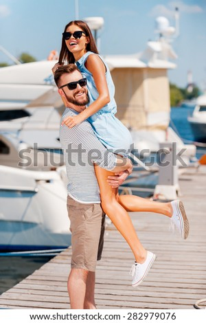Playful summer couple. Happy young man picking up his beautiful girlfriendwhile standing on quay  - stock photo