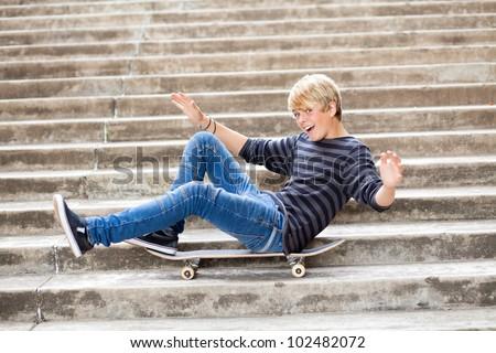 playful teen boy sitting on skateboard - stock photo
