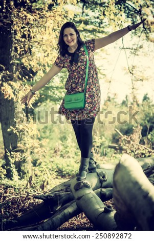 playful woman balancing on a branch, vintage filter effect added  - stock photo
