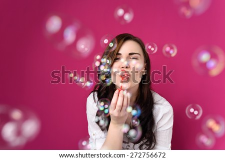 Playful woman blowing party bubbles at the camera as she celebrates a special occasion or birthday, over magenta - stock photo