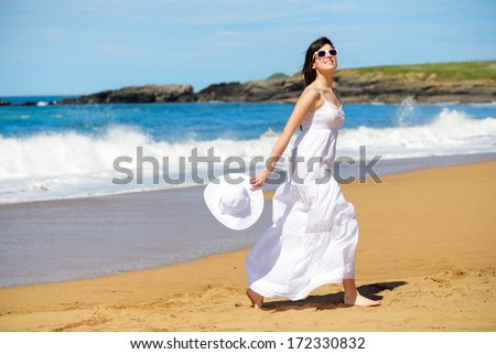 Playful woman on beach summer vacation dancing and having fun. Joyful girl on relaxing summertime walk. Asturias, Spain. - stock photo