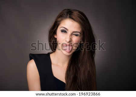 Playful woman sticking her tongue out - stock photo