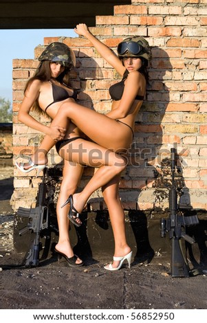 Playful women in military helmets near the brick wall