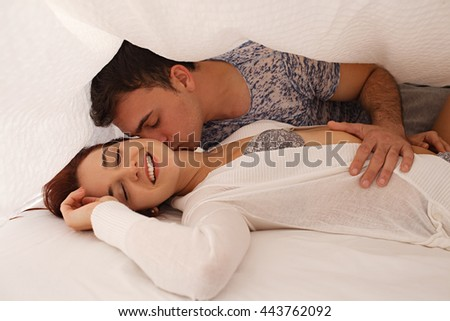 Playful young beautiful couple laying under white linen in bed, hugging kissing with romance, passion and desire, home interior. Boyfriend and girlfriend lovers together in bedroom, indoors lifestyle. - stock photo