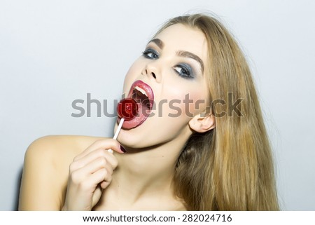 Playful young blonde girl portrait with bright make up looking forward holding and licking round red sugar candy standing on light gray background copyspace, horizontal picture - stock photo