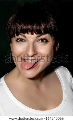 Playful young brunette making a funny face with tongue. - stock photo