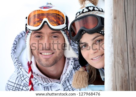 Playful young couple enjoying their skiing holiday - stock photo