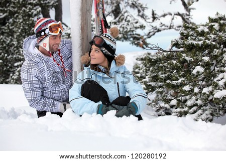 Playful young couple stood by their snowy chalet - stock photo