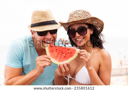 playful young couple with slice of watermelon on summer holiday - stock photo