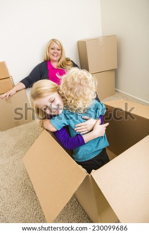 Playful Young Family In Empty Room Playing With Moving Boxes. - stock photo