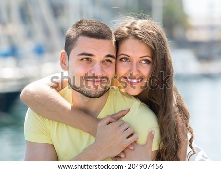 Playful young girl and her boyfriend smiling against sea in sunny day - stock photo