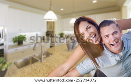 Playful Young Military Couple Inside Home with Beautiful Custom Kitchen. - stock photo