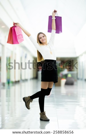 Playful young woman dancing with shopping bags happy and excited. Sale, discount, fashion, profitable offer concepts - stock photo