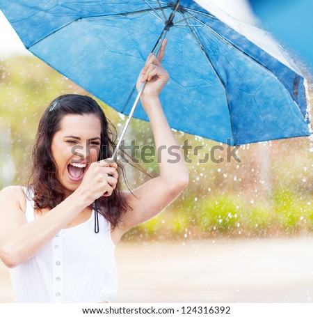 playful young woman holding umbrella in the rain - stock photo
