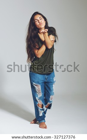 Playful young woman in designer jeans and t-shirt standing barefoot blowing a kiss as she flirts with the camera - stock photo