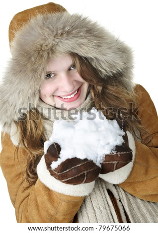 Playful young woman in winter coat with fur hood holding pile of fresh snow