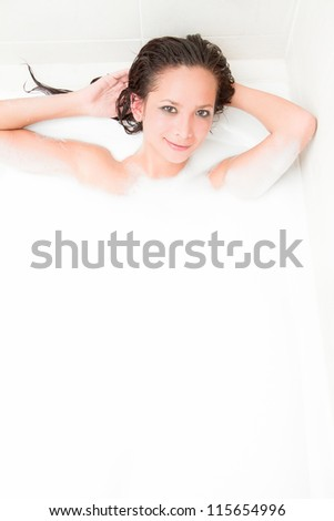 Playful young woman on a foam bath in the tub