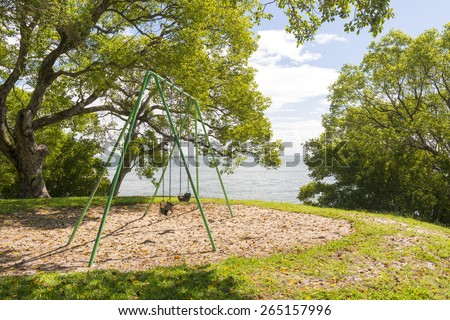 Playground equipment swings for children next to the sea, under huge trees - stock photo
