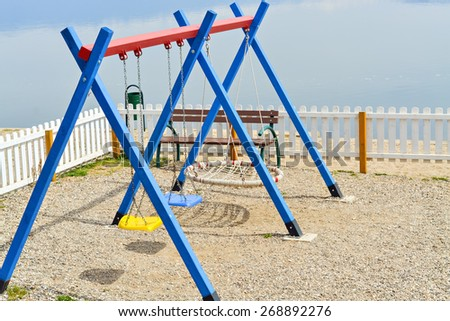 Playground for little children in the park near the lake with toys in vivid colors - stock photo