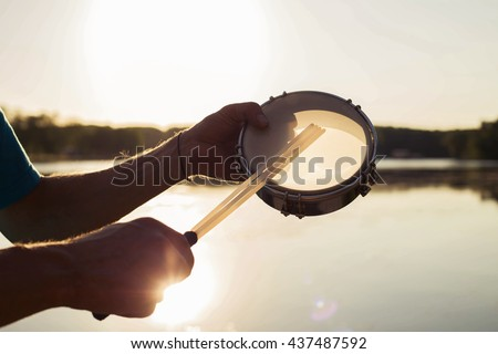 playing a musical instrument tambourine on background sky at sunset - stock photo