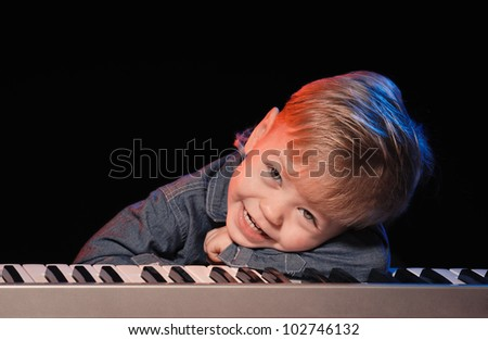 playing and singing little boy on black background - stock photo