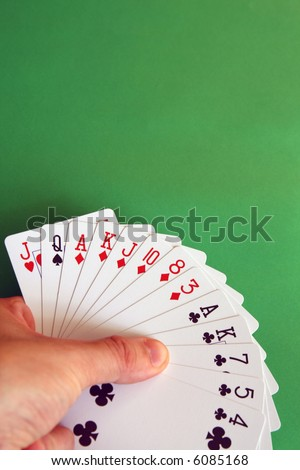 playing bridge - one hand (Q spade, J heart, A,K,J,10,8,3 diamonds, A,K,7,5,4 clubs)  background green, selective focus - stock photo